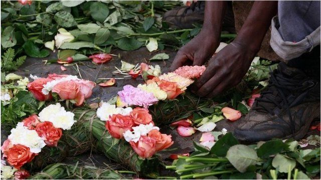 A trader prepares flowers in the shape of a cross for sale outside the City Mortuary