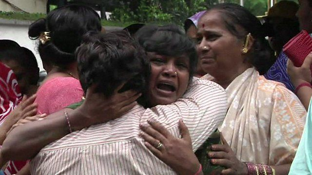 A woman is comforted near the collapsed building