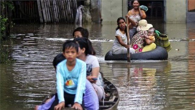 People make their way through a flooded area near the Mekong river in Phnom Penh October 1, 2013