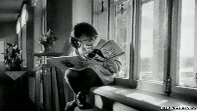 Child sitting on a windowsill, reading a book