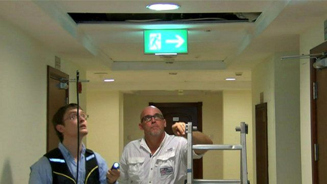 Men inspect hole in ceiling