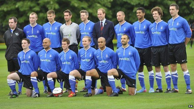 """The Duke of Cambridge stands with members of the Polytechnic FC prior to their match against the Civil Service FC, in the grounds of Buckingham Palace""""s garden"""