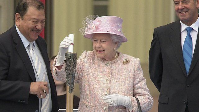 The Queen inserts her message into the Commonwealth baton; she'll read it at the opening ceremony of the games.