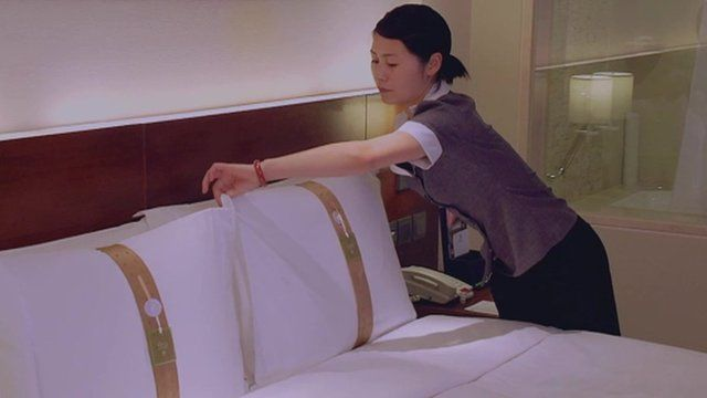 Hotel worker turning down bed