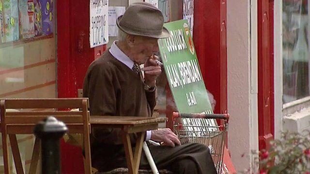 Old man smokes outside shop