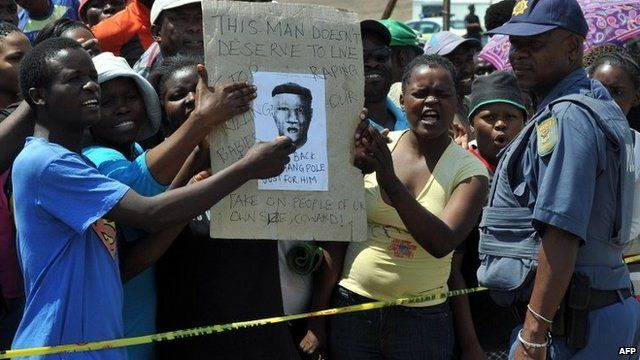 A police officer by protesters demonstrating in Diepsloot, north of Johannesburg, over the rape and murder of two toddlers - Friday 18 October 2013