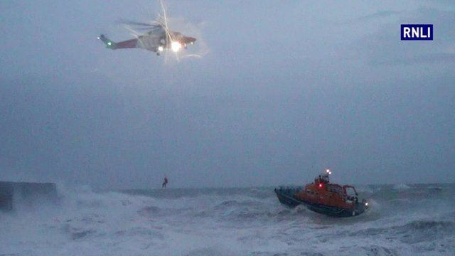 Helicopter and lifeboat in stormy seas