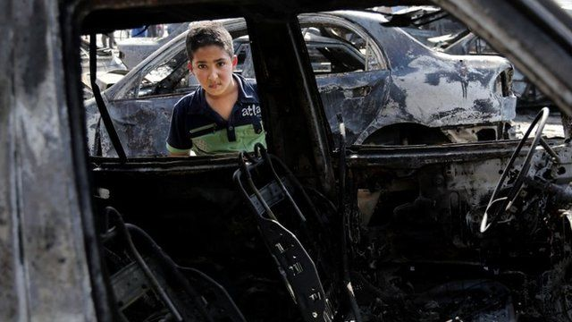 """A boy inspects a destroyed car after a car bomb attack hit the Sha""""ab neighbourhood of Baghdad"""