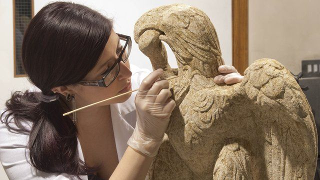 A conservator at the Museum of London Archaeology cleans a sculpture of a Minories eagle and serpent found in London