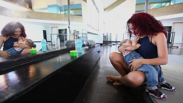 Woman breastfeeding child in a dance studio