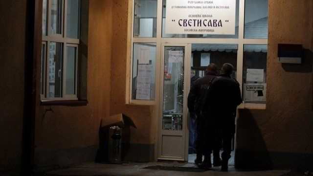 Kosovo police officers inspect vandalised polling station in Mitrovica