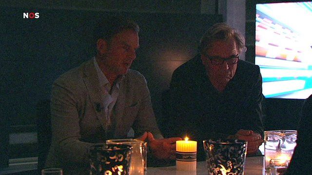 Sports pundit discuss the action by candlelight