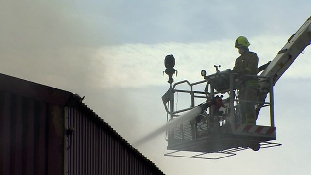 Firefighter with a hose on a hydraulic platform