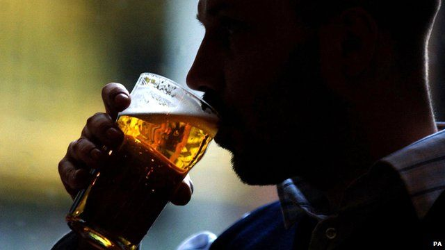Anonymous man drinking pint of beer