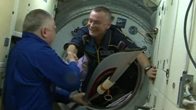 Expedition 37 commander Fyodor Yurchikhin (L) shakes hands with Expedition 38 cosmonaut Mikhail Tyurin after Tyurin handed over the Olympic torch