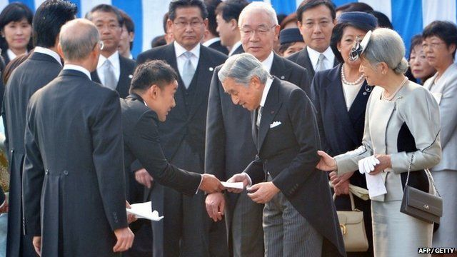 Japanese actor and politician Taro Yamamoto (3rd L) hands a letter to Emperor Akihito (front C) during the annual autumn garden party at the Akasaka Palace imperial garden in Tokyo on October 31, 2013.