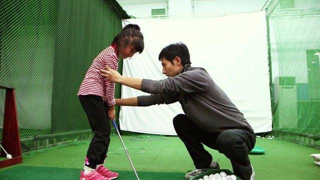 A coach adjusts a child's stance