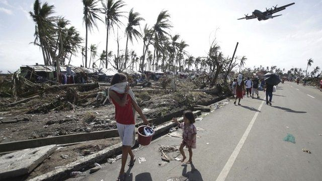 Survivors look at a military C-130 plane which arrives at typhoon-ravaged Tacloban city