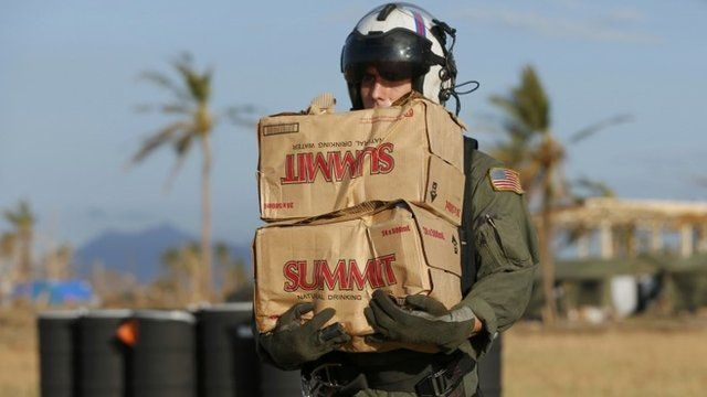 U.S. Marine carries packages of drinking water to a waiting helicopter to be deployed to survivors of Super Typhoon Haiyan at Tacloban airport