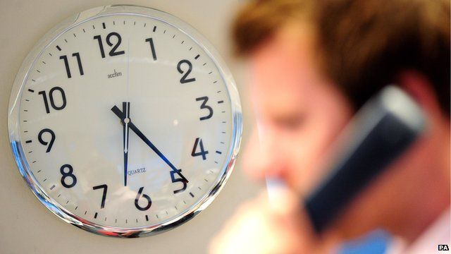 Worker on the phone with a clock in the background