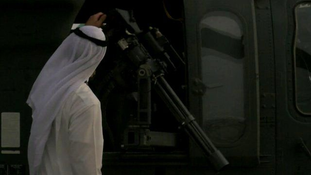 Middle eastern man inspecting a machine gun