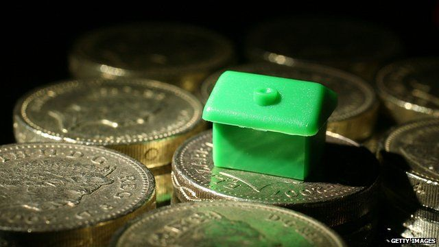 A monopoly board house resting on pound coins