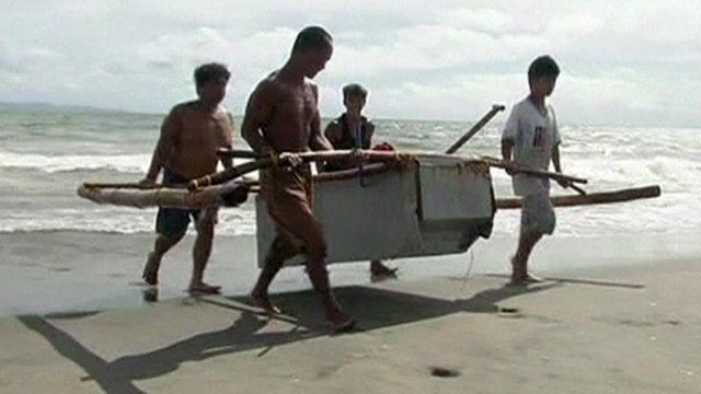 A fridge boat being lifted on to a beach