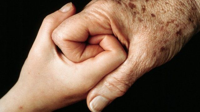 younger and older person holding hands