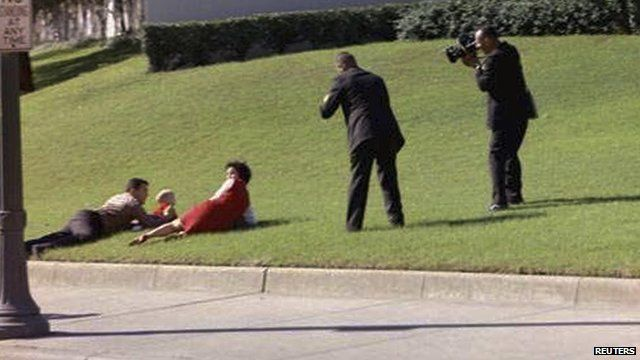 Bill and Gayle Newman covering their children after shots were fired at President Kennedy