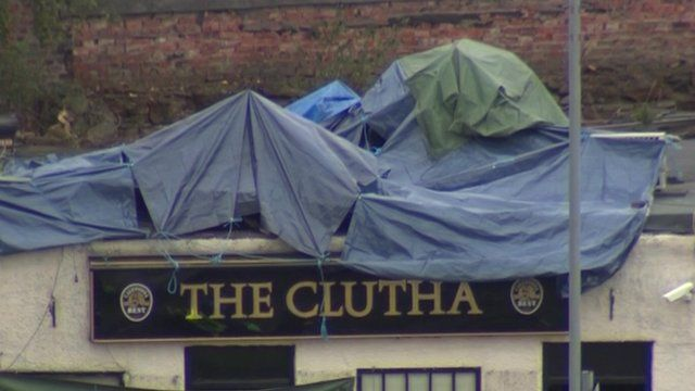 Wreckage on pub roof, covered in tarpaulin