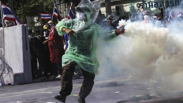 An anti-government protester throws back a teargas canister towards police during clashes near the metropolitan police headquarters in Bangkok December 2, 2013