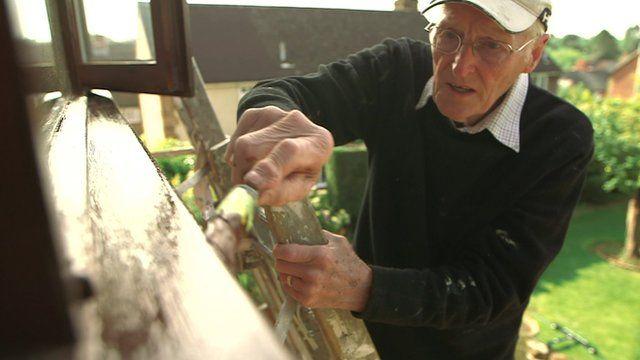 Older man painting window