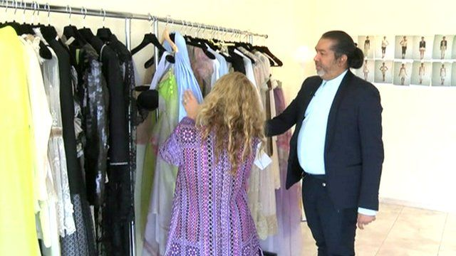 Essa Walla looks at rail of dresses