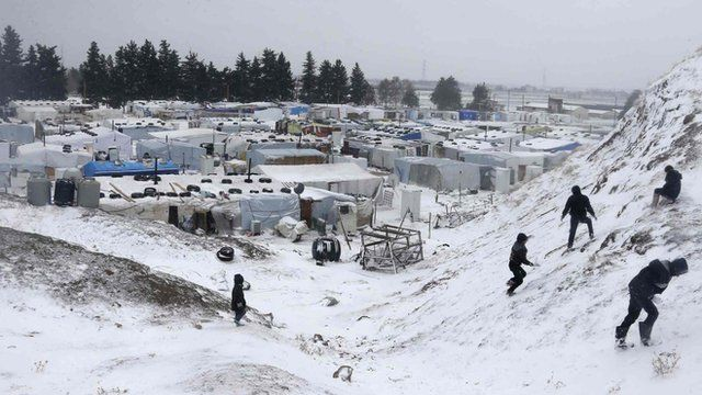 Children play in the snow in refugee a camp
