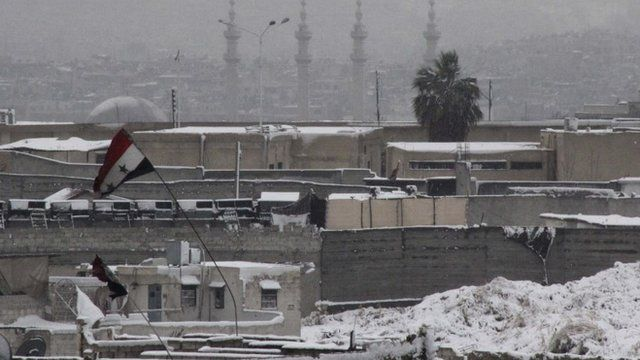 A Syrian national flag is seen on a building covered with snow in the city of Aleppo December 11 ,2013
