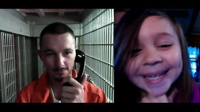 A daughter speaks to her inmate father via video-link in prison