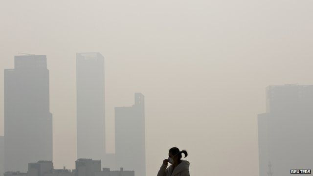 A woman on the street in Shanghai, with buildings obscured by smog