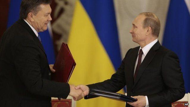 Russian President Vladimir Putin (right) and Ukrainian President Viktor Yanukovych shake hands in Moscow