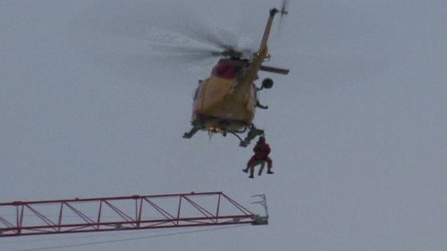The helicopter lifts the man to safety