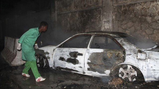 A firefighter looks at a destroyed car at the scene of an explosion outside the Jazeera hotel in Mogadishu, January 1, 2014