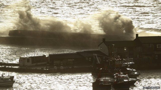 Waves break over the Cobb sea wall at Lyme Regis