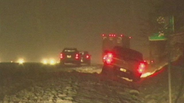 Cars driving - and on the side of the road - in heavy snow in Virginia, US