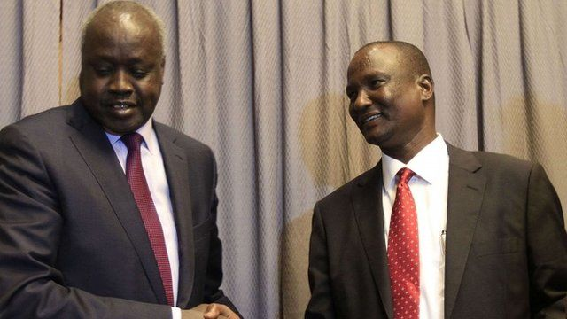 South Sudanese rebel delegation chief Taban Deng (R) shakes hands with South Sudanese leader of the government's delegation Nial Deng Nial