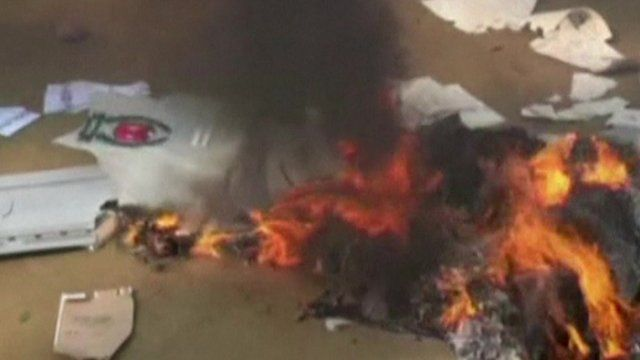 Smashed ballot box and burning voting papers
