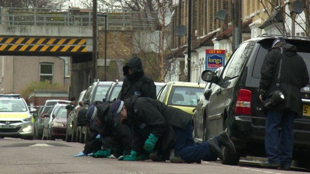 Officers examine the scene of the double stabbing