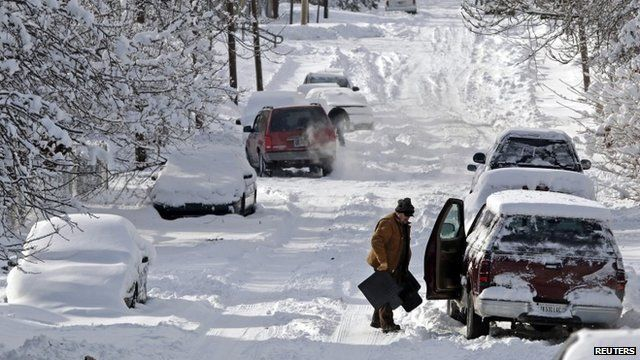 A man clears snow from his car in Indianapolis, Indiana January 6, 2014