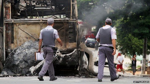 Policemen pass by a burnt bus