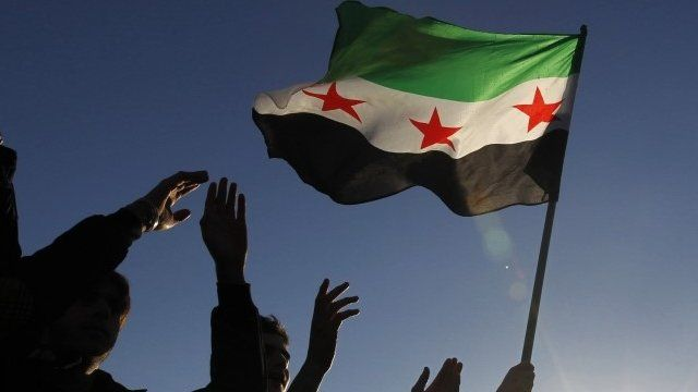 Syrian refugees hold the Syrian opposition flag