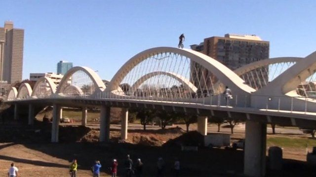 Biker rides along the top of a curved bridge