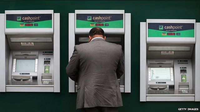 A customer uses a cash machine at Lloyds Bank branch